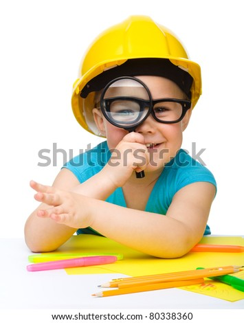 Cute little girl is looking through magnifier wearing hard hat, isolated over white - stock photo