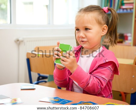 Cute little girl is playing with educational cards while sitting at table - stock photo