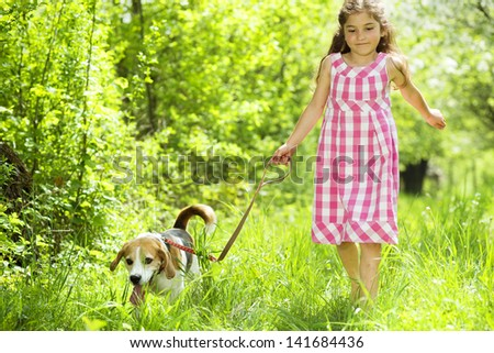 Cute little girl is playing with her dog in the green park - stock photo