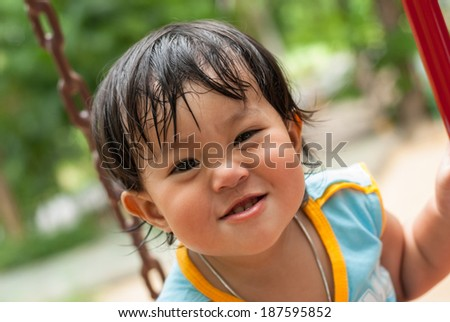 Cute little girl is playing with leaves in  park - stock photo