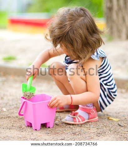 Cute little girl is playing with sand in playground, outdoor shoot - stock photo