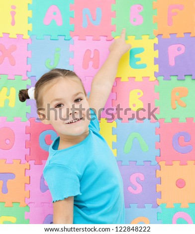 Cute little girl is pointing at letter B - stock photo