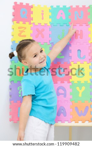 Cute little girl is pointing at letter N - stock photo