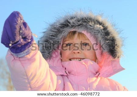 Cute little girl is pointing her hand in a winter