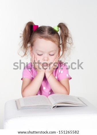 Cute little girl is reading a book, isolated over white - stock photo
