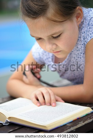 Cute little girl is reading a book while laying on bench