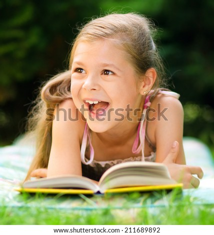 Cute little girl is reading a book while laying on green grass - stock photo