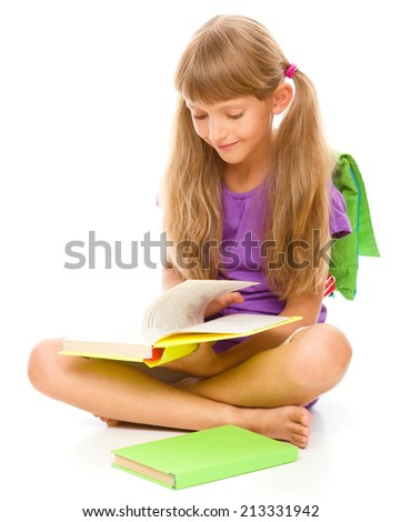 Cute little girl is reading a book while sitting on floor, isolated over white - stock photo
