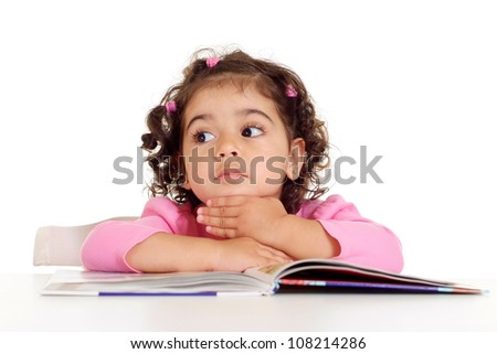 Cute little girl is reading sitting at the table
