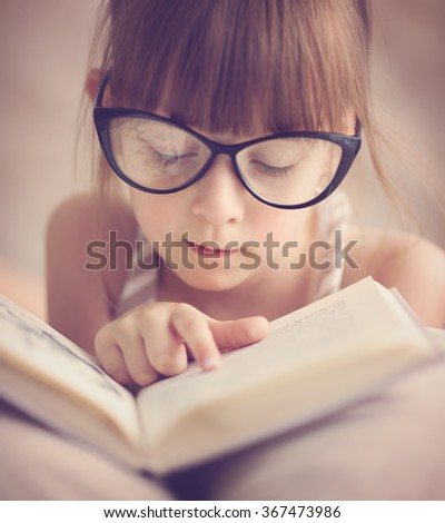 cute little girl is reading the book - stock photo