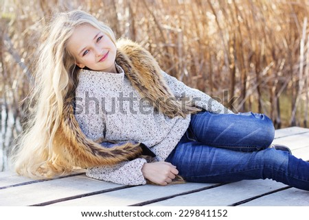 Cute little girl is resting near lake - stock photo