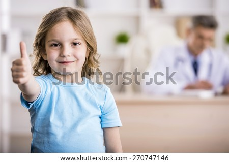 Cute little girl is showing thumb up. Doctor is sitting on background. - stock photo