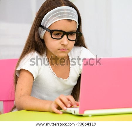 Cute little girl is sitting at table with her pink laptop and wearing glasses