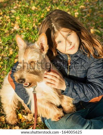 Cute little girl is sitting on the grass and keeps your dog Scottish Terrier