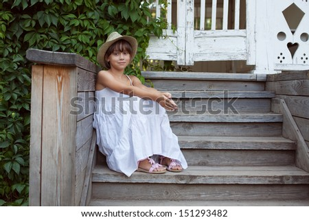 Cute little girl is sitting on the porch steps - stock photo