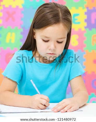 Cute little girl is writing using a pen - stock photo