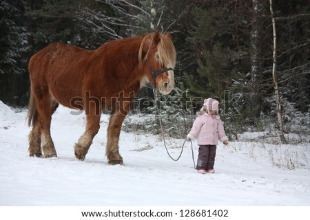 Cute little girl leading big draught horse by the forest in winter - stock photo
