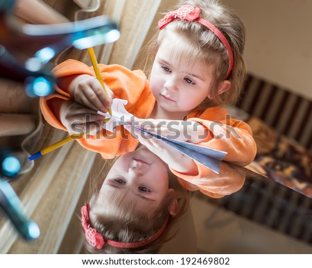 cute little girl learns to write with a pen at home - stock photo