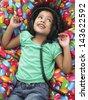Cute little girl listening music through headphones while lying on beanbag - stock photo