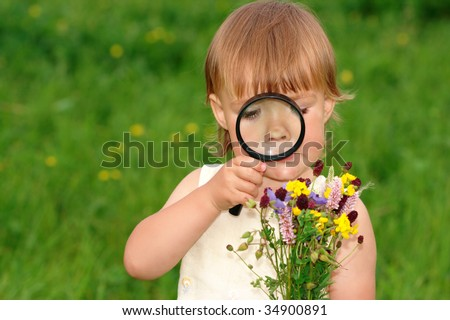 Cute little girl looking at bouquet of field flowers through magnifying glass - stock photo