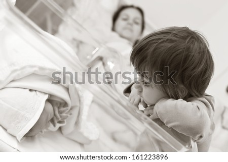 Cute little girl looking at the new-born little brother in the hospital - their mother in the background  - stock photo