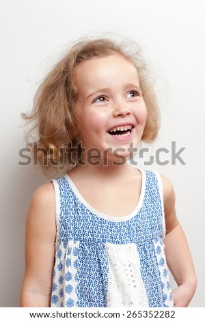 Cute little girl looking surprised. She laughs and looks up on a background white wall. - stock photo