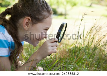 Cute little girl looking through magnifying glass on a sunny day - stock photo