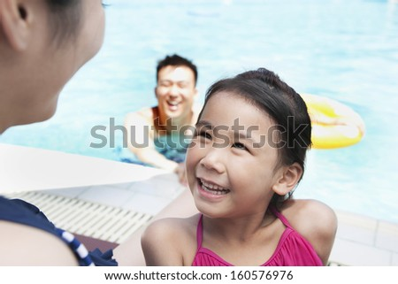 Cute little girl looking up at her mother by pool - stock photo