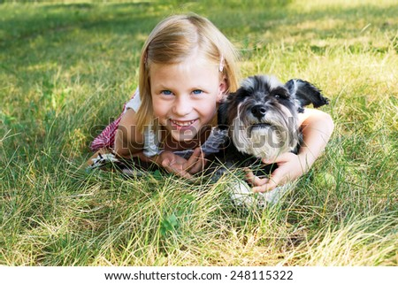 Cute little girl lying on the grass in the park, beside her dog - stock photo