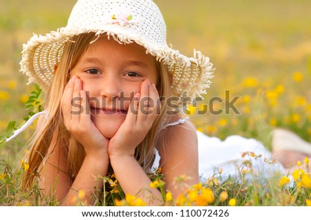 Cute little girl lying on the meadow on sunny summer day. - stock photo