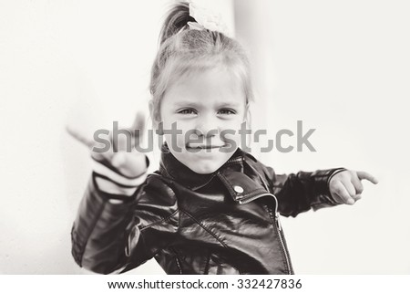 cute little girl making a rock-n-roll sign