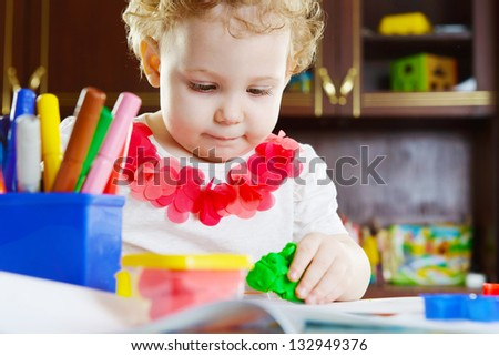 Cute little girl making a star shape from clay dough - stock photo