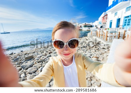 Cute little girl making selfieat Little Venice popular tourist area on Mykonos island, Greece - stock photo