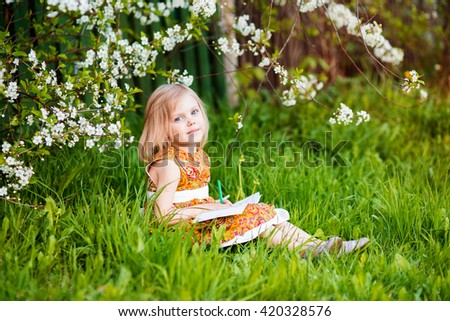 cute little girl near blooming apple trees and cherry drawing pencils - stock photo