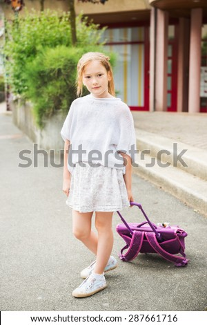 Cute little girl of 7 years girl walking to school, carry backpack with wheels - stock photo