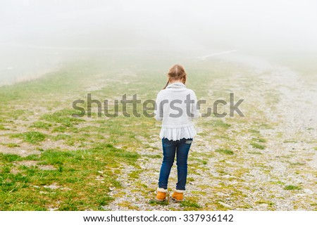 Cute little girl of 8 years old playing outdoors on a very foggy day, wearing grey warm pullover, back view