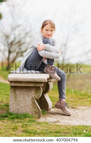 Cute little girl of 8-9 years old sitting on the bench outdoors, wearing grey jeans and cardigan - stock photo