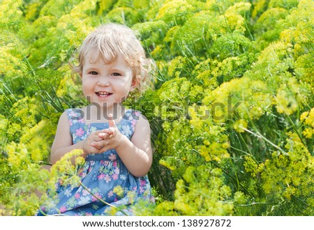 Cute little girl on a background of flowers of dill on a summer day