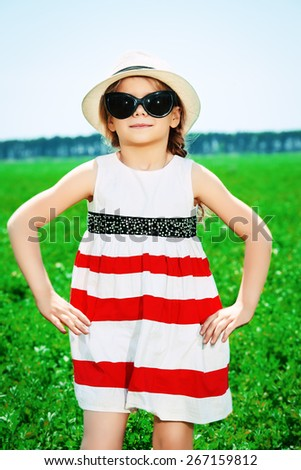 Cute little girl on a meadow in summer day. Happy childhood.  - stock photo