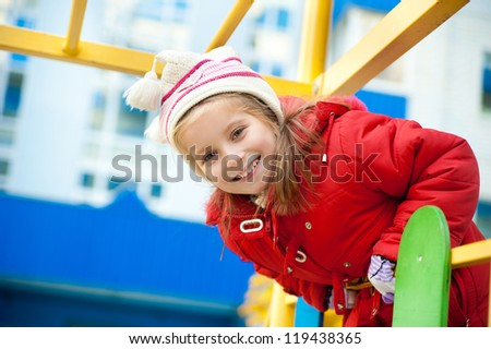 Cute little girl on outdoor playground looking at camera