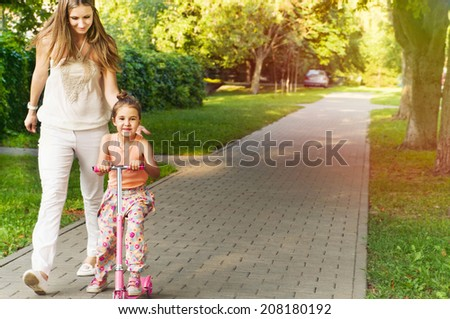 cute little girl on scooter have fun with mother in the park in summer sunny day - stock photo