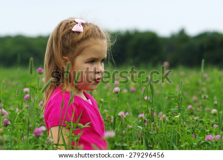 Cute little girl on the meadow in spring day.