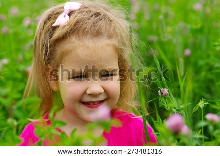 Cute little girl on the meadow in spring day. Child on field . - stock photo