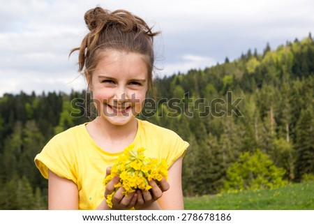 Cute little girl on the meadow with flower - stock photo