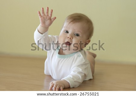 Cute little girl or baby on floor gives a wave