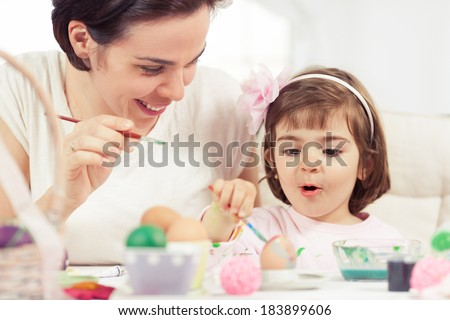 Cute little girl painting Easter eggs with mommy. Toned image. - stock photo