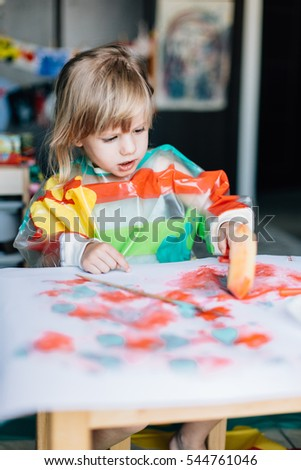 Cute little girl painting with a paint roller using gauche paints.