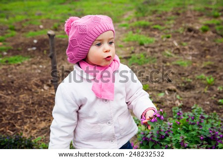 cute little girl picking flowers in the meadow in spring day outdoors,