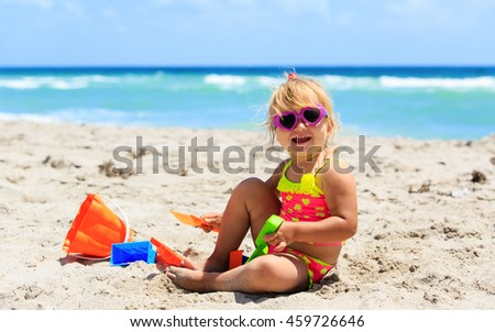 cute little girl play with sand on beach