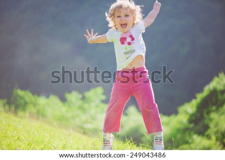 Cute little girl playing at sunny green meadow - stock photo